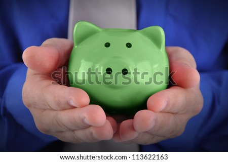 A business man is holding a bright green piggy bank in his hands for a money or finance concept. - stock photo