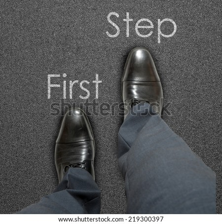 A business man is looking down at his feet and there is a text First step, new business concept - stock photo