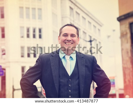 A business man is standing outside of a city looking happy and confident for a occupation or corporate concept. - stock photo