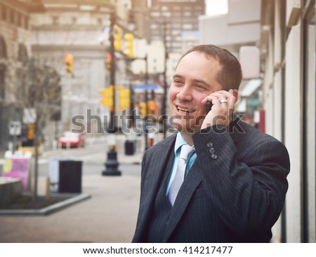 A business man is talking on a cell phone outside in a city and he is wearing a suit and smiling for a success or communication concept. - stock photo