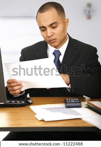a business man looking at paper work in his office - stock photo