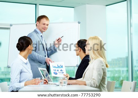 A business man showing something on a whiteboard to his colleagues - stock photo