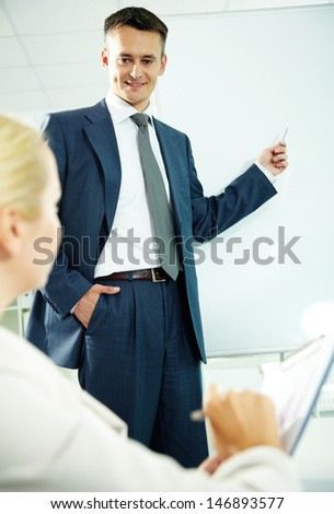 A business man showing something to his co-worker on a whiteboard - stock photo