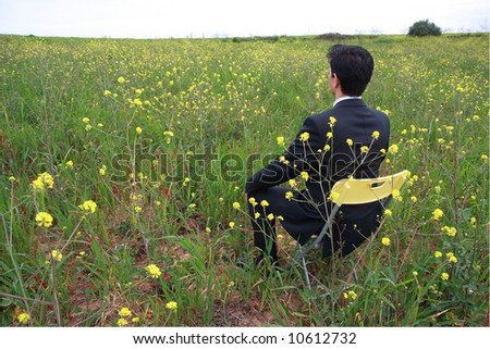 A business man sitting in a field with flowers - stock photo