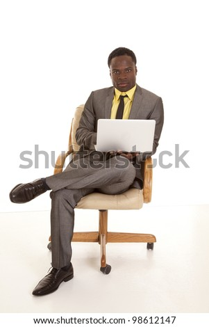 a business man sitting on his chair working on his laptop with a serious expression on his face. - stock photo