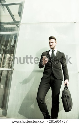 A business man standing in front of a modern office building. - stock photo