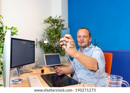 A business man taking a selfie in his clean and paperless office. - stock photo