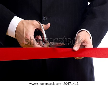 A business man wearing a blue suit cutting a red ribbon with a pair of shiny silver scissors.  Grand opening ceremony or event - stock photo
