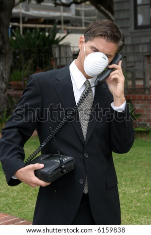 a business man wears a medical face mask or dust mask to protect himself and others from the flu and other airborn virusis while talking on his 1980s era car phone - stock photo