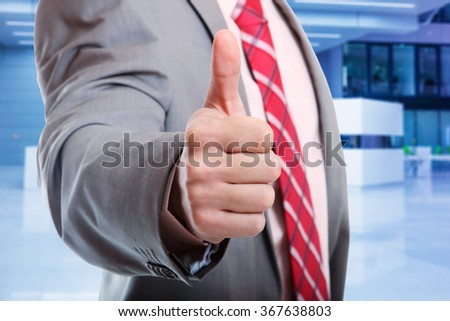 A business man with thumb up light business background - stock photo