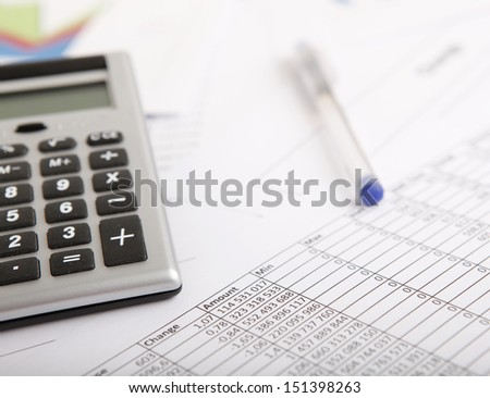 A business strategy concept with a calculator and color charts - stock photo