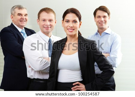 A business team of four looking at camera and smiling - stock photo