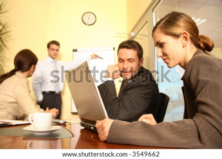 A business team of two men and two women work together with a laptop and a flip chart in a conference room to prepare a new business proposal for a client. - stock photo