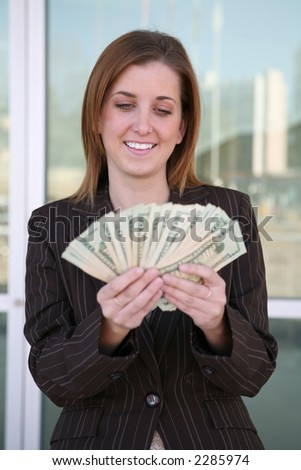 A business woman holding a lot of money - stock photo