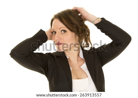 A business woman in her jacket and white shirt with her arms up by her hair. - stock photo