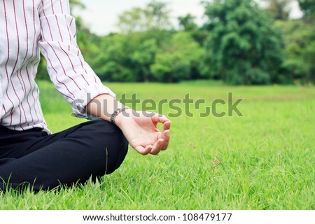 A business woman relax in a park in the lotus position in close-up - stock photo