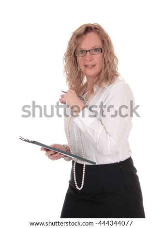 A business woman standing in a black skirt white blouse holdingher clipboard, looking into the camera, isolated for white background. - stock photo