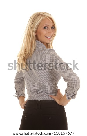 A business woman with her back to the camera looking over her shoulder with a smile on her face. - stock photo