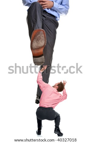 A businessman about to be stepped on by a giant foot, isolated on a white background. - stock photo