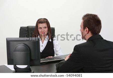 A businessman and a businesswoman at an interview in an office. - stock photo