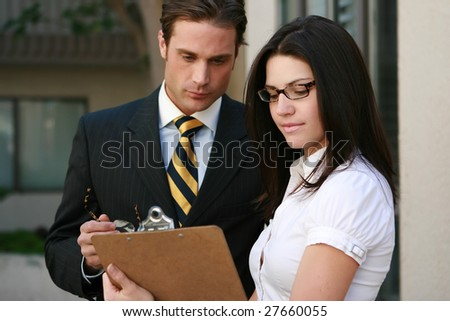 A businessman and businesswoman review notes - stock photo