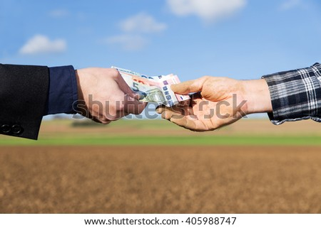 a businessman and farmer with a money transfer - stock photo