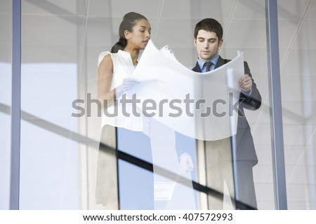 A businessman and woman discussing plans or blueprints - stock photo