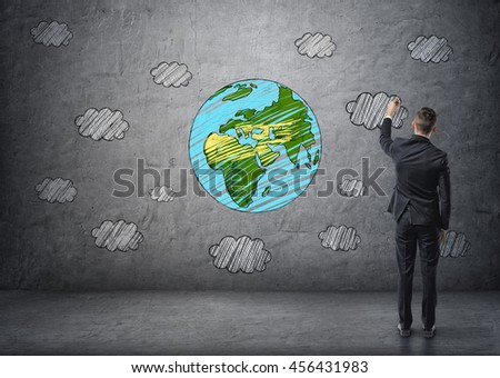 A businessman drawing the Earth and clouds in colour on the concrete wall. Exploring the planet. A world of possibilities. Taking chances. - stock photo