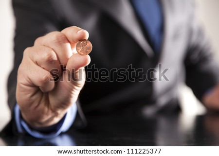 A businessman dressed in a suit holds a shiny penny in his hand. - stock photo