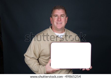 A businessman dresses in business casual clothing displays a blank whiteboard.  Whiteboard is blank to allow designers to place copy. - stock photo