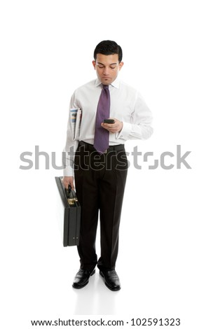 A businessman either making a phone call or reading or sending a sms text message, - stock photo