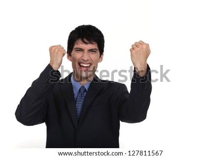 A businessman gesturing victory. - stock photo