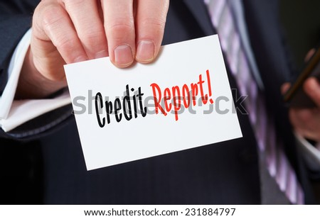 A businessman holding a business card with the words,  Credit Report, written on it. - stock photo