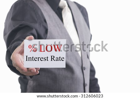A businessman holding a business card with the words, Low Interest Rates, written on it. - stock photo