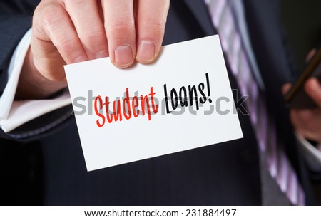 A businessman holding a business card with the words, Student Loans, written on it. - stock photo
