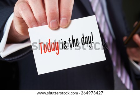 A businessman holding a business card with the words,  Today is the Day! - stock photo