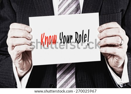 A businessman holding a card with the words, Know Your Role, written on it. - stock photo