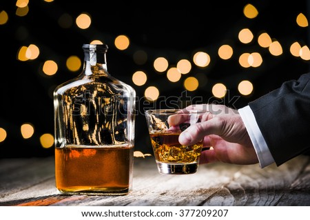 a businessman holding a glass of whiskey. - stock photo
