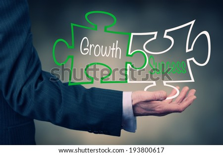 A Businessman holding a growth success puzzle concept. - stock photo