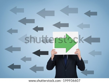 A businessman holding a poster with opposite arrow sign. It is a concept of individualism rather than collectivism in employment relationships or entrepreneur practice. - stock photo