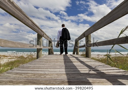 A businessman holding his shoes and jacket stands barefoot on a jetty looking across a beach to a blue sea - stock photo
