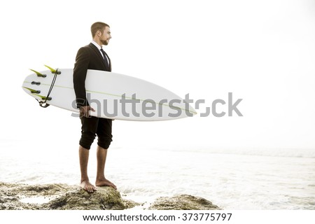 A Businessman holding is surfboard after a long day of work - stock photo