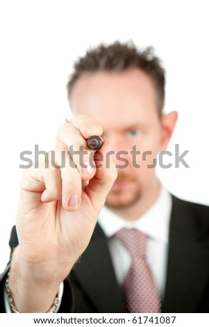 A businessman holds up a black marker pen in line with his eye.  Differential focus on the hand and pen.  Studio isolated on a white background. - stock photo