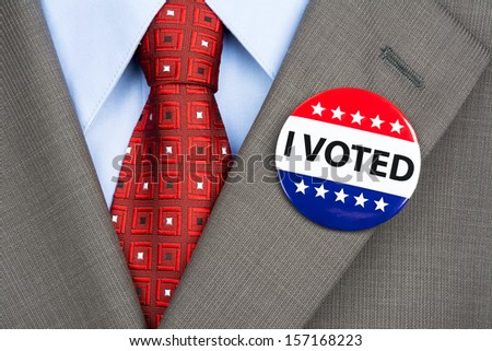 A businessman in a tan suit wearing his vote pin on his jacket lapel - stock photo