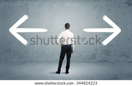 A businessman in doubt, having to shoose between two different choices indicated by arrows pointing in opposite direction concept - stock photo