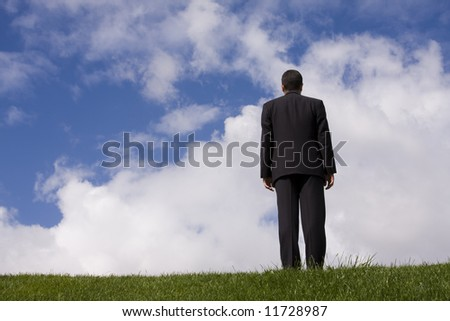 a businessman in the field going to some place - stock photo