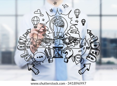 A businessman is drawing a business plan development sketch on the glass screen. A modern panoramic office in blur on the background. A light bulb as a concept of brainstorm. - stock photo