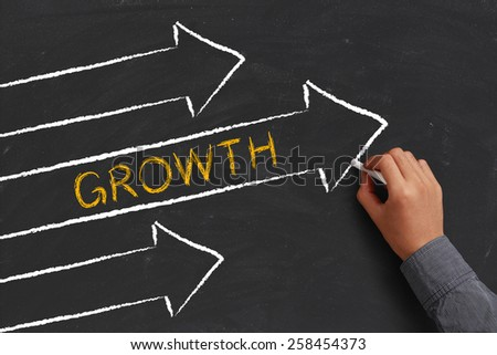 A businessman is drawing Growth concept with arrows on blackboard. - stock photo