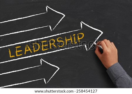 A businessman is drawing Leadership concept with arrows on blackboard. - stock photo