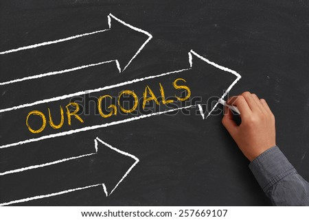 A businessman is drawing Our Goals concept with arrows on blackboard. - stock photo
